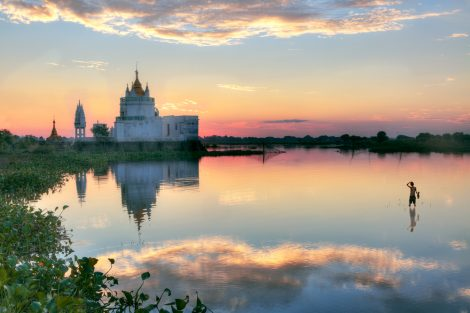 Buddhist temple at sunset reflecting in lake near U bein bridge at Amarapura, Mandalay, Myanmar