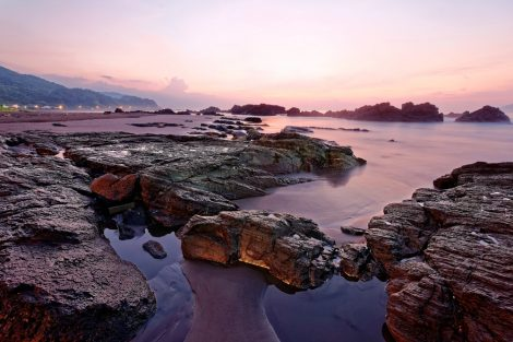 Beautiful sunrise sky reflecting on the peaceful sea water at the rocky beach of Yilan Coast Geologic Park